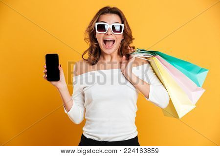 Photo of happy young lady standing isolated over yellow background holding shopping bags. Looking camera showing display of phone.