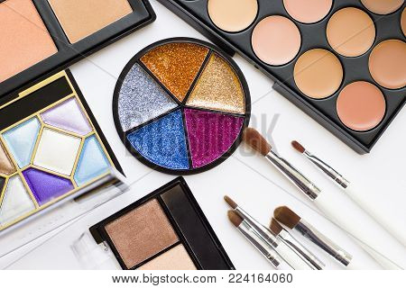 Make Up Beauty Fashion Concept Mock up. A set of professional make up products: eyeshadows, eye and lip glitter, face foundation, concealer, contouring, brushes, top view, flat lay