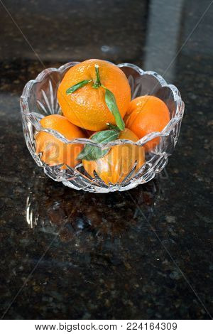 Several small mandarin oranges fill a transparent cut glass bowl and casts shadows on the black granite counter.