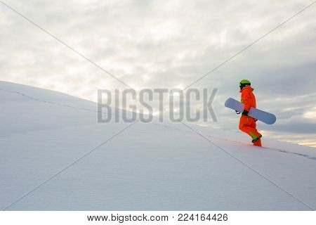 Snowboarder with his bord climbing on the top of ski slope