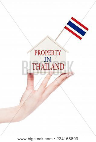 Female hand holding wooden house model with Thailand flag on top Property in Thailand