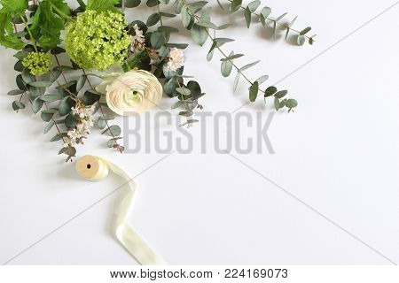 Feminine wedding, birthday desktop mock-up scene. Blank paper greeting card and bouquet of eucalyptus branches, pink roses and Persian buttercup flowers, white table background. Flat lay, top view.