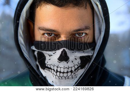 Closeup winter portrait of the man with expressive eyes in the hood and mask with skull - anonymous rebel.