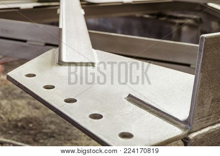 Jointing shaped element of galvanized metal construction close-up. Limited depth of field. poster