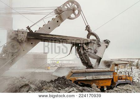 Heavy excavator loads slag into a big mining dump truck. Work in heavy industry.