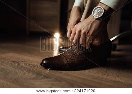 The groom is gathering in the morning. A gray chair. Men's Black classic patent leather shoes. Wedding details. The groom ties up the shoelaces.