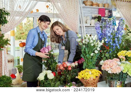Women flower sellers. Two attractive young women working in flower shop and enjoying in beautiful flowers. Female sales assistant working as florist and holding bouquet with with roses happily looks at camera