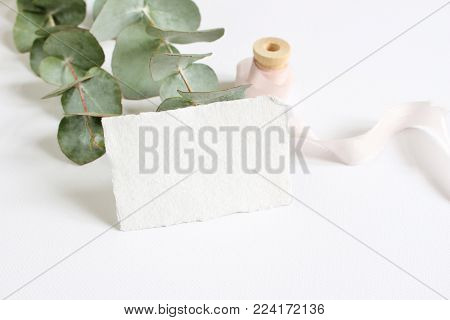 Bright feminine spring stationery mockup scene with a handmade paper greeting card, spool of silk ribbon and eucalyptus leaves on a white table background, wedding styled stock photography.