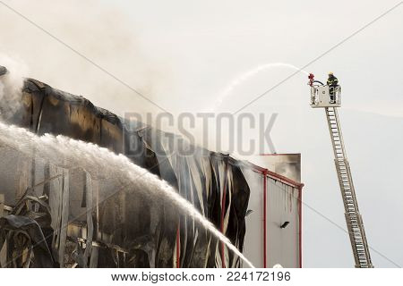 Fire disaster in a warehouse. Fire fighting in an industrial area.