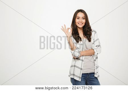 Portrait of optimistic satisfied woman with long brown hair posing on camera and showing OK sign, isolated over white background