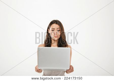 Image of young woman 30s looking on screen of her silver notebook thinking or expressing misunderstanding with face isolated over white wall
