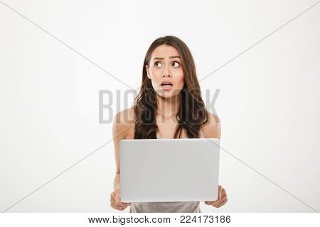 Image of young woman 30s looking away being stressed or disappointed while using silver notebook in hand isolated over white wall