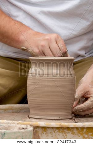 hands of a potter throwing clay