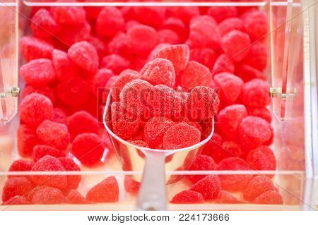 Heap of flavored red rubber candy. Raspberry jelly beans. Assorted candies in a candy buffet.