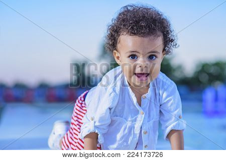 Mixed race baby girl playing next to a fountain sprinkler, enjoying a warm day outside on sunset