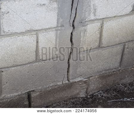 A crack in the concrete wall. The destruction of the wall from the gray blocks.