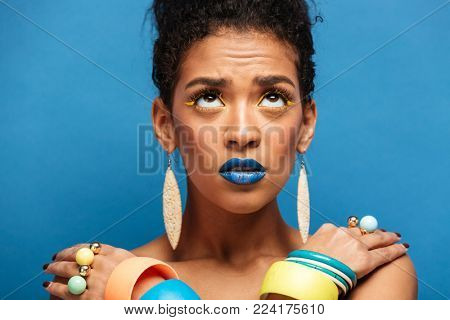 Colorful photo of thrilled mixed-race woman with trendy makeup and accessories looking upward with crossed hands on shoulders over blue wall