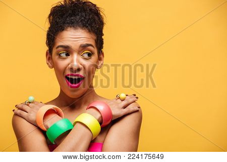 Gorgeous afro american woman in colorful adornment embarrassing while posing on camera half-naked with crossed hands on shoulders over yellow copy space