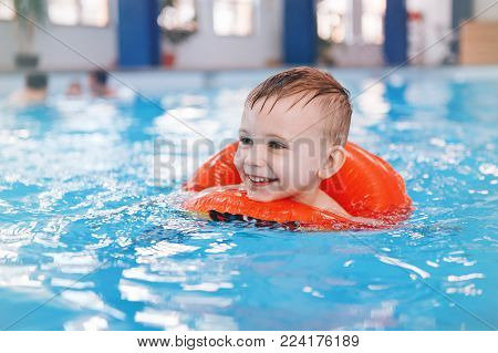 Portrait of happy white Caucasian child in swimming pool. Preschool boy training to float with red circle ring in water. Healthy active lifestyle