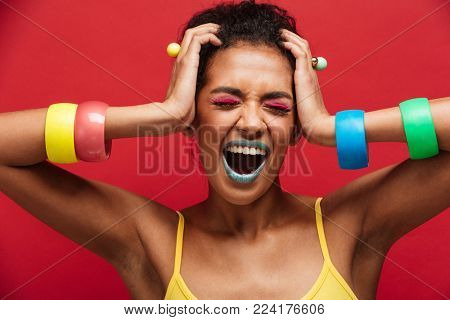 Image of young woman in colorful accessories being stylish grabbing her head and screaming with closed eyes over red background