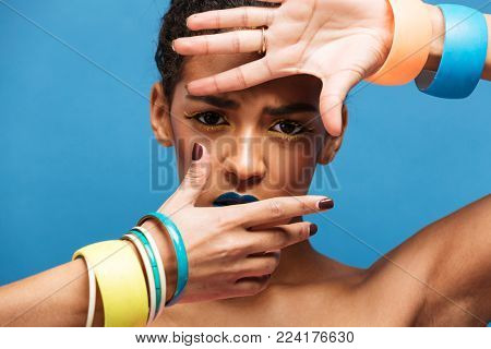 Trendy portrait of scared or thrilled woman with trendy makeup and accessories covering face with hands over blue background