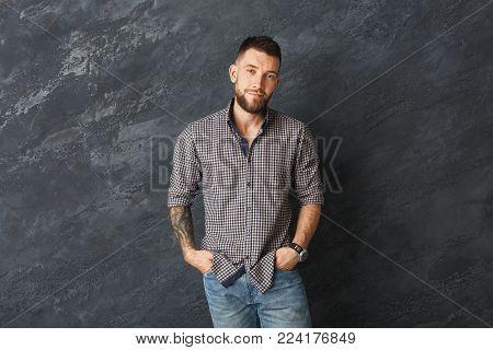 Handsome smiling man posing. Fashion boy on grey background, studio shot, copy space