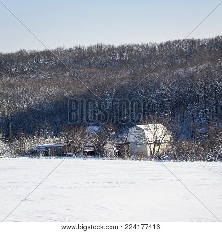 house in a village on the outskirts of a winter forest all around covered by white snow