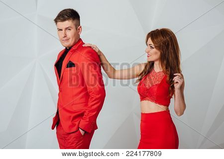 casual couple leaning against a white wall, man with hands in his pockets looking at the woman . woman looking at the camera while leaning on his shoulder