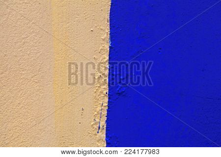 Old wall painted yellow and blue colors. Textured background of grunge stucco wall painted with yellow and blue colors