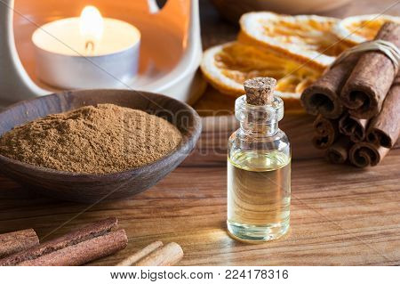 A bottle of cinnamon essential oil with cinnamon sticks, cinnamon powder and an aroma lamp