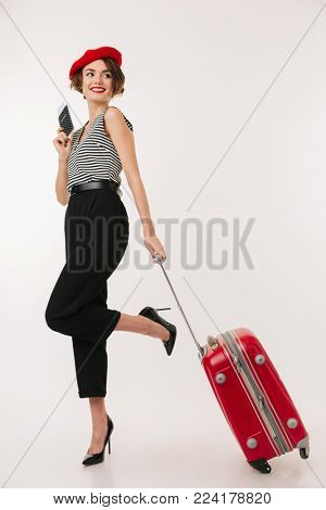 Full length portrait of a smiling woman wearing red beret walking with a suitcase while holding passport and looking away isolated over white background