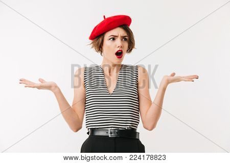 Portrait of a confused woman wearing red beret shrugging shoulders isolated over white background