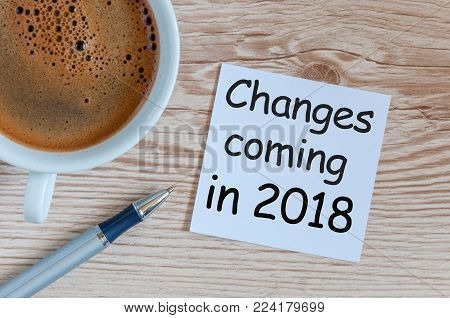 change is coming in 2018. text in message at workplace with morning coffee cup.