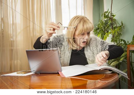 Senior blond woman forgot the time, late for her deadline, covered with work and documents