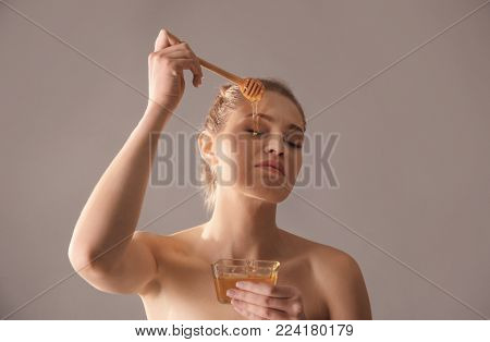 Beautiful young woman applying honey on her face against color background