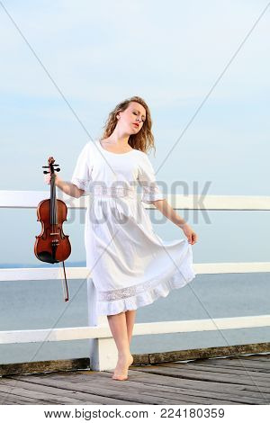 The blonde girl music lover on pier with a violin. Love of music concept.