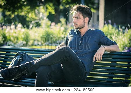 One handsome young man in urban setting in European city, a city park