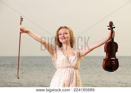 Happy crazy blonde girl music lover on beach with a violin. Love of music concept.