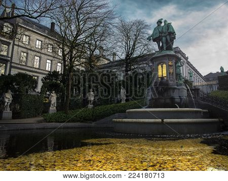 Brussels / Belgium - November 25th 2017: The small quiet Zavelsquare park in Brussels with the Statue of Counts Egmont and Hoorn on top of a fountain with the Egmont palace in the background.