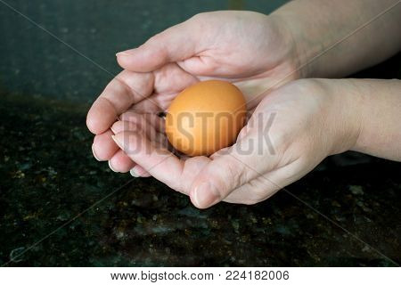 A woman's hands are cradling a fragile brown eggs.