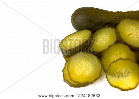 Marinated cucumber isolated on white background. One whole pickled cucumber and a few chopped cucumber slices on a white background.