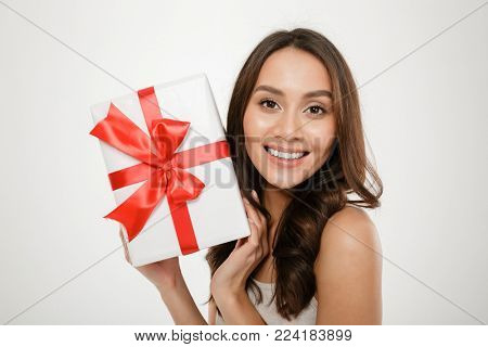 Close up photo of cheerful woman showing gift-wrapped box with red bow on camera expressing happiness and delight isolated over white background