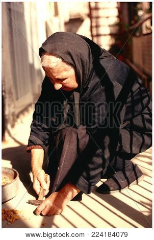 A Close Up Photo Of A Grandmother While Breaking Almonds, Dressed In Traditional Uniform.