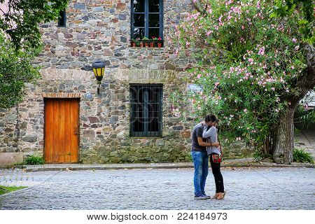 COLONIA DEL SACRAMENTO, URUGUAY - DECEMBER 7: Unidentified people hug in front of an old house on December 7, 2014 in Colonia del Sacramento, Uruguay. It is one of the oldest towns in Uruguay.