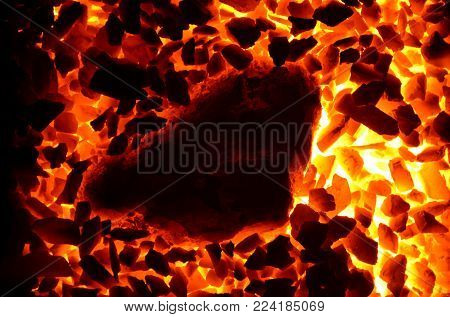 Burning charcoal anthracite shallow fraction is surrounded by a huge piece.