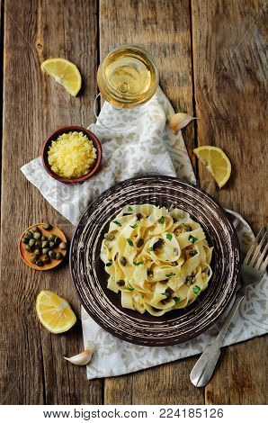 Pasta with Garlic Butter Caper Sauce on a wood background