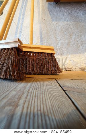 Close up large brooms for house work on old wooden floor of country house. Sweeping