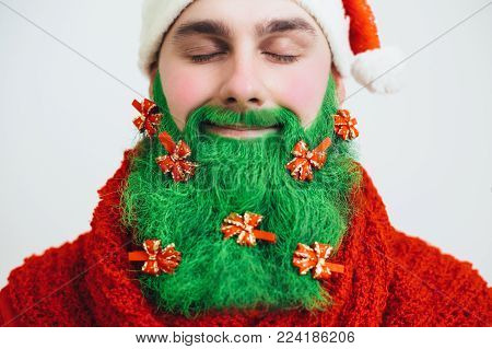 Santa Clause in red clothes with green beard decorated with red bows smiles and show ok sign