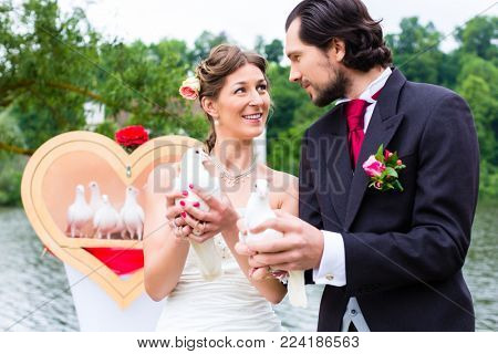 Happy bridal couple at wedding with white doves