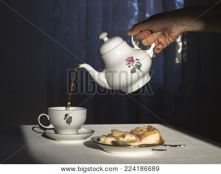The hand holds the kettle and pours the tea in a cup in the sunlight